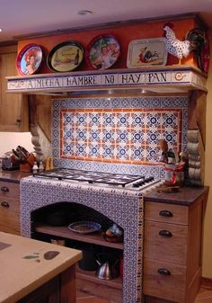"Even though it's from Santa Fe, the ceramic tile surrounding the cooktop has a Spanish spirit. The hood mantel supports a display of vibrant trays from Mexican beer makers. The tile across the front is inscribed with the Spanish proverb, ""A mucha hambre no hay pan duro,"" which roughly translates to, ""When very hungry, there is no stale bread."" For your inspiration. (Source: kitchens.com 