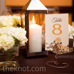 Small square vases of white hydrangeas decorated the tables, alongside metal lanterns and floral table numbers.