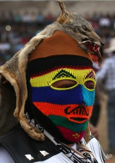 """In this Dec. 25, 2015 photo, a masked fighter wears a dead fox hat before the start of the """"Takanakuy"""" fighting ritual event on the outskirts of Lima, Peru on Christmas day. One of the fighters explained they wear dead animals for a more intimidating look. (AP Photo/Martin Mejia)"""
