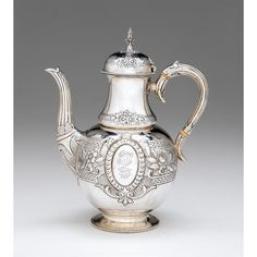 Victorian silver coffee pot  Mappin & Webb, London, 1869-70  Bellied form, decorated with repoussé-worked floral blossoms between two bands of circular medallions, each side with central oval cartouche, one engraved with monogram, the other with family crest, raised on circular pedestal foot with beaded edge, with hinged domed cover.