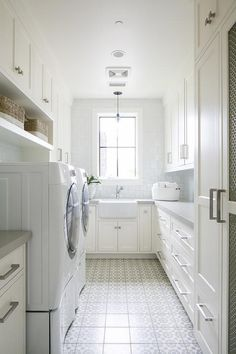 Lovely gray and white laundry room is clad in white and gray mosaic floor tiles placed beneath a white front loading washer and dryer positioned beneath shelves located under shelves mounted under white shaker cabinets. White Laundry Rooms, Mudroom Laundry Room, Laundry Room Remodel, Laundry Room Cabinets, Laundry Room Organization, Laundry Room Design, Armoires Shaker, Küchen Design, House Design
