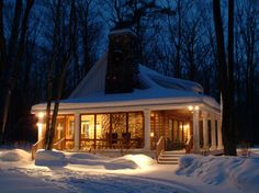 Snowy cabin in the woods lit up at night.