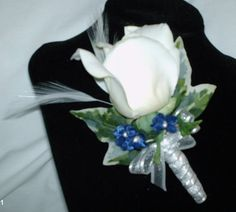 White true touch rose boutonniere with white feathers and sapphire blue accent flowers wrapped in white ribbon trimmed with silver. One large true touch ivy leaf and small ivy leaves surround the rose for the finishing touch.