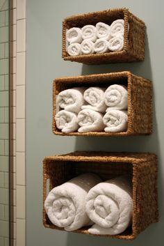 Wall-mounted Towel Storage Baskets ~ I love this!! I want to do this in the space between the shelves above the toilet and the medicine cabinet above the sink.