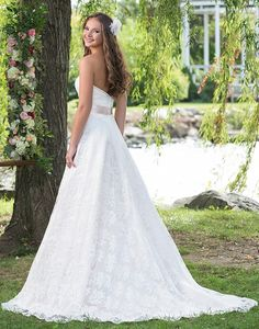 A sweetheart A-line gown with a draped organza bodice, natural waistline, and allover lace and tulle skirt. The attached satin belt at your natural waist adds a pop of color.