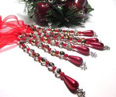 Vánoční ozdoba - rampouch Vánoční ozdona. délka 12 cm. Broušené korálky , červené korálky,Vosková perlička ve tvaru slzy. Zakončeno postříbřenou vločkou. K zavěšení na stromeček , větvičku.Červená stužka.