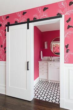 A white barn door on oil rubbed bronze rails is partially framed by pink and black wallpaper finished with lower wall wainscoting.