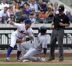 Game #49 5/27/12: New York Mets third baseman David Wright, left, reacts as San Diego Padres' Jesus Guzman, center, is caught trying to steal third while umpire Chris Guccione, right, looks on during the seventh inning of the baseball game on Sunday, May 27, 2012, at Citi Field in New York. (AP Photo/Seth Wenig).
