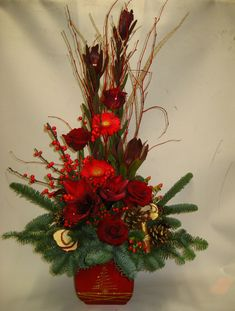 Seasonal, festive floral arrangement in brilliant reds with dried fruit, berries, cones, cinnamon, pine and flowers. Christmas Arrangements, Floral Arrangements, Christmas Flowers, Christmas Wreaths, Dried Fruit, Pine, Cinnamon, Festive, Berries