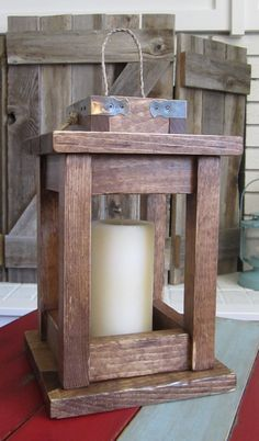"""Natural wood lantern with hardware accents and braided rope handle. 7.5""""x12"""""""