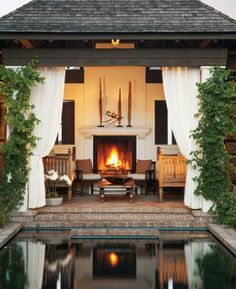 Outdoor bedroom with fireplace and curtain walls.