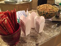 Asian noodles with chopsticks and tiny to go boxes.