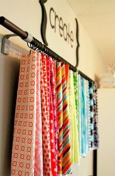 This website has great ideas on how to organize fabric. This is my favorite! Just slide circle rings on a curtain rod and clip.