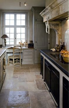 Great color and texture combination - rustic stone floor with distressed wood island and refined gray cabinets.