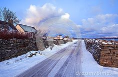 Snow covered single track road to Melness with cloudscape background in winter, Scotland.