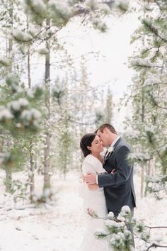 A peek through the snowy trees catches this bride and groom's love.