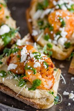 This cajun shrimp hummus crostini is the perfect summer appetizer. Toasted bread topped with hummus, microgreens, shrimp, cilantro pesto and feta cheese.