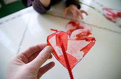 Be Still My Heart Take wax paper, a marker, glue, water and colored tissue paper (red, pink and white). Mix equal parts glue and water on a paper plate. Then tear up small pieces of tissue paper. On the wax paper, draw a heart Dip the tissue paper into the mixture then put it on the heart. Once it's done, let it dry.  Cut out the heart shape, punch some holes in it and string up ribbon so it can be hung