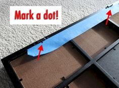 Use painter's tape to measure length of picture frame and line up where nails should go on the wall.