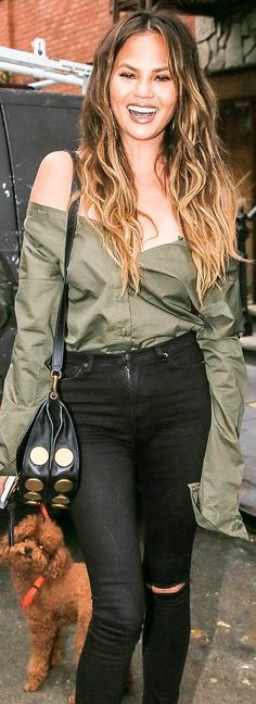 Who made Chrissy Teigen's green off the shoulder top, skinny ripped jeans, and black suede handbag?