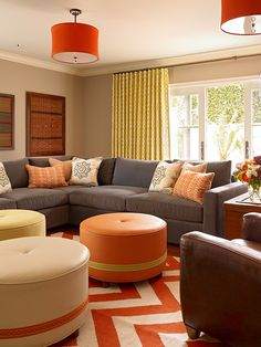 great colors...love the chevron rug, pattern on the drapes, and  orange drum lighting!