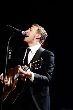 Chris, playing guitar, wearing a suit