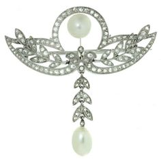 """Edwardian  Antique Garland Style Diamond Pearl Platinum Brooch Pendant. An stunning and elegant Edwardian brooch accented with 2 freshwater cultured pearls, made in 950 and set with an estimated 1.0 carat of sparkling H-I VS1-VS2 old mine-cut diamonds as well as two freshwater cultured pearls. This timeless classic can also be worn as a pendant on a chain. Measurements: 1.41"""" (36mm) width, 1.49"""" (38mm) length. c 1910"""