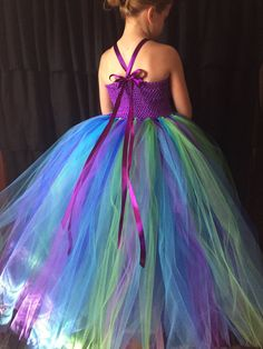 This flower girl dress is just stunning. Perfect for your peacock wedding! It is made with purple, turquoise, kelly green and royal blue tulle that is floor length and empire waisted. The peacock and turquoise feathers are attached to the purple crochet top with an accented jewel piece. The