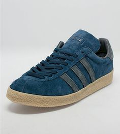 adidas Topanga: adidas Originals presents this Topanga taking inspiration from the Adidas Florida OG. The shoe is presented in a navy suede upper with black leather three stripe branding to the side walls. The shoe is sat on a gum midsole with textured foxing and is finished with a black leather heel panel, branding to the tongue plus tonal navy flat laces.