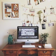 Beautiful workspace, wooden desk, iMac and pegged photographs.