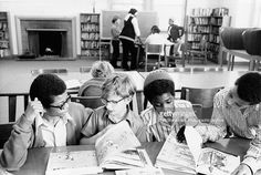An African American teacher assists three boys studying in a Berkeley, California classroom. The Berkeley school district was one of the first to desegregate voluntarily using busing.