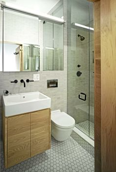 Bad2. Eierne av dette badet har lekt seg med ulike fliser på gulv og vegger, kombinert med innredning i hvitt og tre. Store speil skaper større romfølelse.