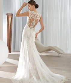 This sultry fit n flare, sleeveless gown with a low V-neckline features magnificent beaded lace over tulle and lace embellished low sheer back with button closure.   The flared tulle over lace handkerchief skirt flows into a Chapel length train.