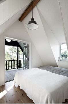 Attic Bedroom Design Ideas; With The Concept Of A Bright, White Color Wall Paint, And Windows, As Well As A Balcony Door On The Side, Making A More Visible Area And Suitable To Rest With Friends
