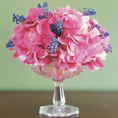 Hydrangeas & Grape Hyacinths - Pink hydrangeas and grape hyacinths clustered in a crystal compote make for a supremely simple arrangement. A hidden grid of floral or transparent tape across the top of the bowl supports the cloud of blooms.
