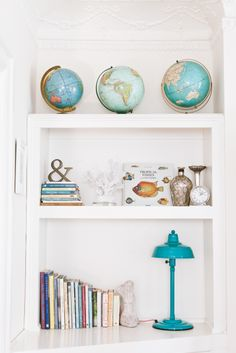 The perfect bookshelf display: Teal Retro Standing Lamp, vintage world globes, coastal collectables