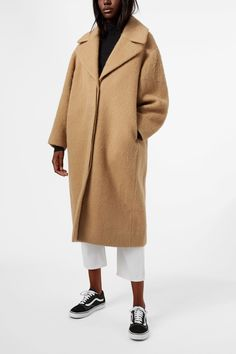 <p>The Mario Coat is a classic coat with a stand collar with big lapels. Made from a fine wool blend, it has a voluminous shape, a concealed button placket