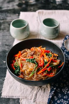 Japchae is a simple Korean noodle dish jampacked with a rainbow of vegetables and accented with a hit of flank steak. It's a recipe that's been requested by many of our readers, so this day is long overdue! Japchae is made with Korean potato starch glass noodles, which are surprisingly light, and (it doesn't happen often …