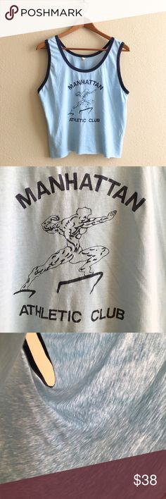 Manhattan Athletic Club Crop Paper thin light blue tank with navy trim. Raw edge on bottom, fits cropped.   BRAND: Screen Stars MATERIAL: 50/50 YEAR/ERA: 80s LABEL SIZE: - BEST FIT: S  MEASUREMENTS: Chest 20 inches Length 21 inches   Trades  Modeling  Check out my closet for more vintage tees! Vintage Tops Tank Tops
