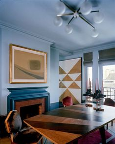 Italian Job: A Parisian Pad Gets a Milano Makeover // blue dining room with black fireplace, midcentury modern chandelier, and geometric artwork // modern dining rooms