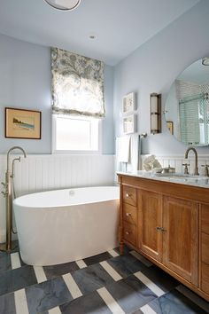 floor tile design, old school mirror, pull down shade, the tub, vanity adds warmth. Sarah Richardson is a bathroom genius.