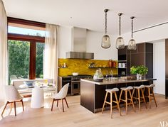 In a Hamptons, New York, home designed by architect Annabelle Selldorf and designer Joe Nahem, a colorful backsplash, pendant lights, and vintage stools enliven the kitchen.