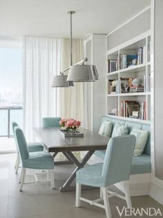 A polished tole pendant fixture and lacquered white millwork add subtle sheen. Fixture, Charles Edwards. Custom table. Custom charis and banquette in Loro Piana linen. Pillows in Manuel Canovas and Baker fabrics. Curtains in Great Plains sheer. Walls in Phillip Jeffries.  INTERIOR DESIGN BY LUIS BUSTAMANTE