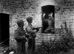 A German sniper surrenders to American soldiers. France, 1944.   (Keystone & Stringer)