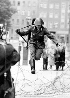 Conrad Schumann, East German solider, jumps the beginnings of the Berlin Wall in 1961