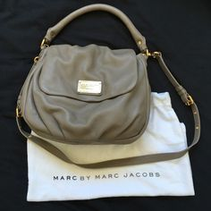 """Marc By Marc Jacobs Lil Ukita bag in warm zinc Marc by Marc Jacobs Lil Ukita leather bag in warm zinc. Magnetic flap closure. One zip pocket and 2 slip pockets inside. Approximately 10.5""""(L)x10""""(H)x3.5""""(D). Small marks to leather, gold hardware tarnished in areas, and small crack to leather handle as shown in pic. Need to look closely to notice. Will include dustbag. Marc by Marc Jacobs Bags"""
