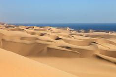 Sandwich Harbour, Fototapete von Christian Camenzind. Die riesigen Sanddünen an der Küste Namibias laufen scheinbar direkt in den Ozean hinein. Diese atemberaubende Landschaft weckt die Sehnsucht nach fernen Ländern. Mit dieser Fototapete genießen Sie diesen traumhaften Anblick Tag für Tag. #wallpaper