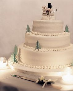 """This winsome wedding cake at Lenore and Lawrence's wedding was decorated with paper trees and """"snowballs"""" piped from frosting and topped with a marzipan snowman and snow-woman holding a replica of the bride's bouquet."""