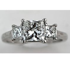 This is how I want to re do my wedding ring down the road! My current center stone on one side, get another version of it to go on the other side, then a bigger diamond in the center. Use the diamonds in my 2 wedding bands and place one on each side like they are now. Maybe add some more diamond to the side of the ring instead of the plain band for more bling! :)