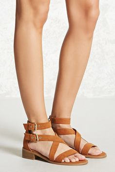 A pair of faux suede sandals featuring a strappy design with a dual ankle buckle closure, back zipper, open toe, and a low stacked heel.